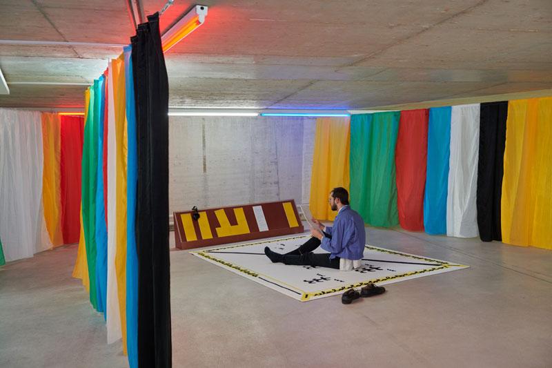 Eine Person sitzt auf einem weiß-schwarz-gelben Teppich zwischen bunten Vorhängen und guckt auf ein Blatt Papier.