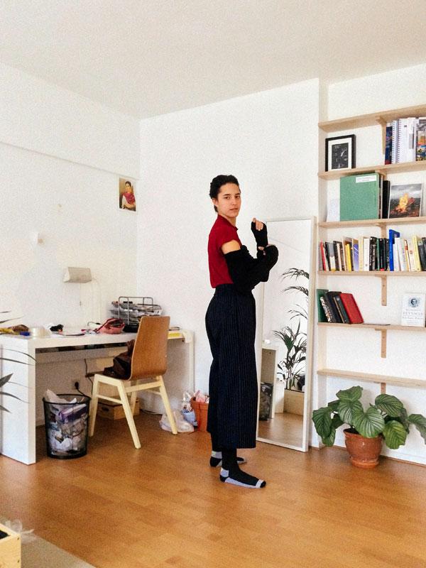 Eine junge Person steht in einem Zimmer mit dem Blick zur Kamera. Im Zimmer sind ein Schreibtisch, ein Spiegel, ein Bücherregal und eine Pflanze zu sehen.