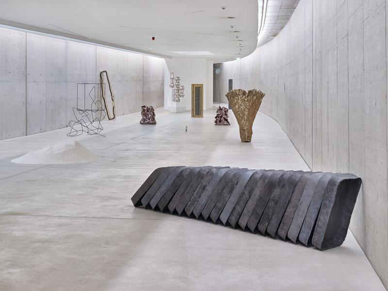 Unterschiedliche Skulpturen stehen im Ausstellungsraum verteilt.