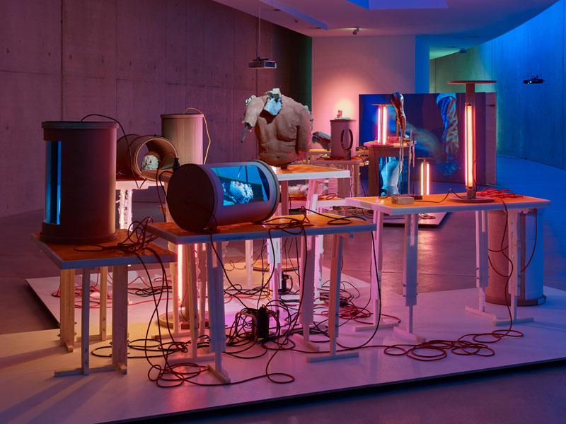Technische Apparate und Skulpturen stehen auf Tischen, von denen Kabel herabhängen. Der Raum ist in farbiges Licht getaucht.
