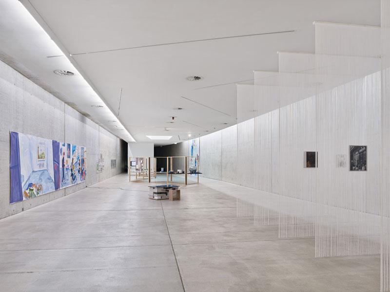 Unterschiedliche Kunstwerke, darunter ein Gemälde und vier Vorhänge aus weißen Fäden