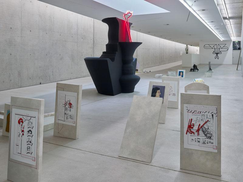 Graue Stelen mit Bildern stehen vor einer schwarzen, überdimensionalen Vasen-Skulptur im Ausstellungsraum.