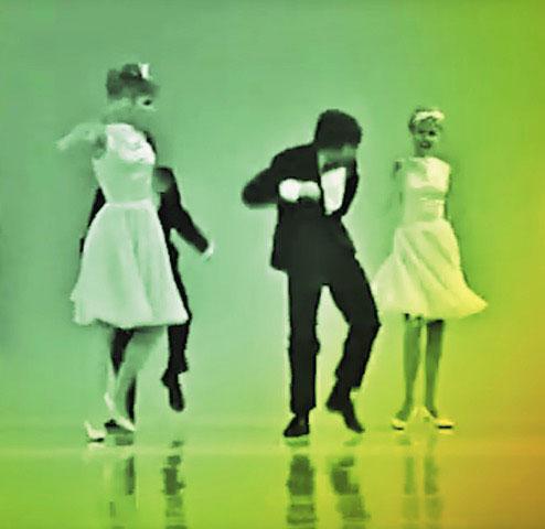 Vor grünem Hintergrund tanzen zwei Männer in Anzügen und zwei Frauen in weißen Kleidern.