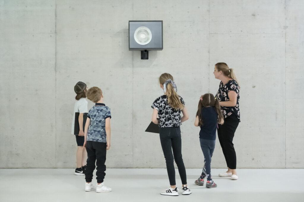 Eine Kunstvermittlerin betrachtet am Familientag mit vier Kindern eine Videoarbeit im KIT.