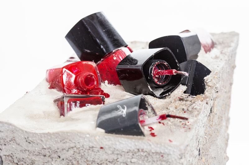 Rote Nagellackfläschen sind halb versenkt in grauem Beton
