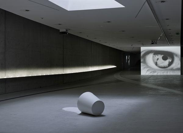 Im dunklen Ausstellungsraum liegt im Vordergrund eine graue eimerförmige Skulptur. Dahinter ist ein Lichtstreifen und eine Projektion zu sehen, auf der ein überdimensionales Auge abgebildet ist.