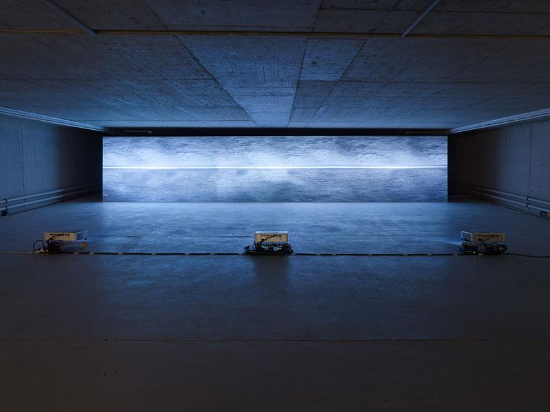 Eine waagerechte Leinwand im dunklen Ausstellungsraum zeigt den gespiegelten Ozean, davor stehen drei Beamer auf dem Boden.