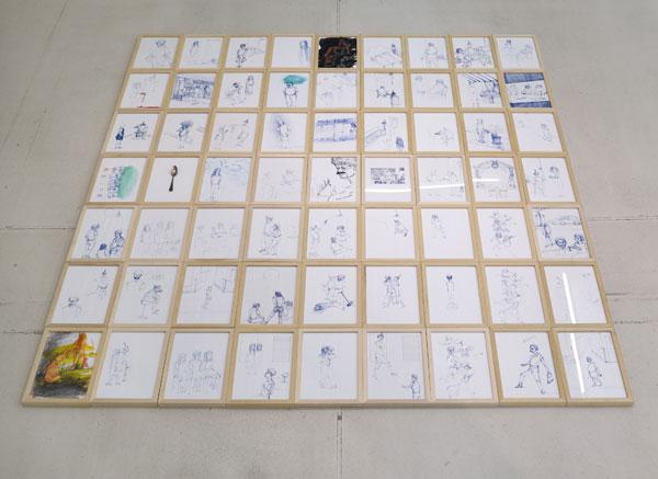 63 kleine gerahmte blaue Zeichnungen liegen auf dem Boden, zwei Zeichnungen sind flächendeckend schwarz oder gelb