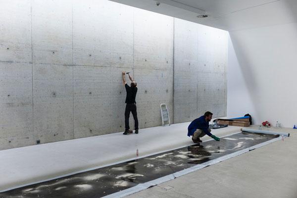 Zwei Personen während des Ausstellungsaufbaus: Eine befestigt einen Nagel an der Wand, die andere hockt an einer langen horizontalen Leinwand, die auf dem Boden liegt.