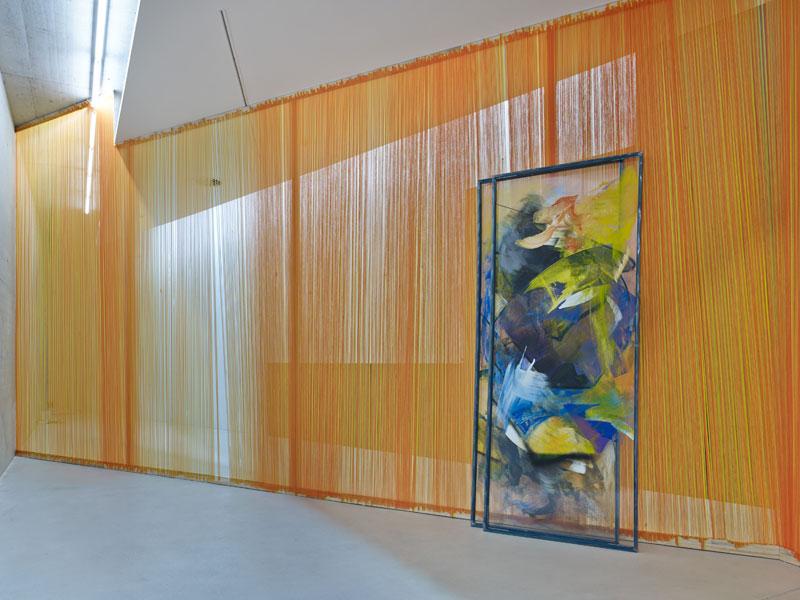 Zwei gerahmte Glasscheiben mit aufgetragener gelber und blauer Farbe stehen vor einem Vorhang aus orangenen Fäden.