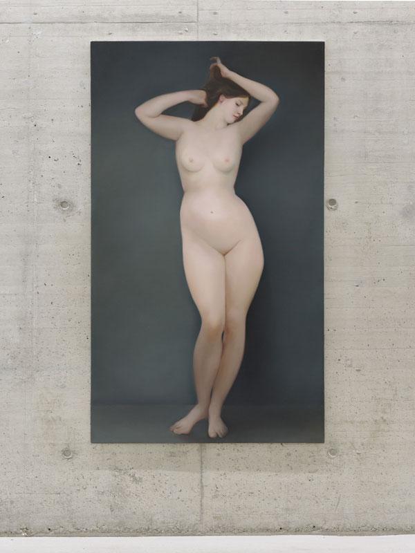 Auf einer großen, dunkelgrauen Leinwand vor grauer Betonwand ist eine junge nackte Frau frontal zu sehen, die sich mit beiden Händen in die Haare greift.
