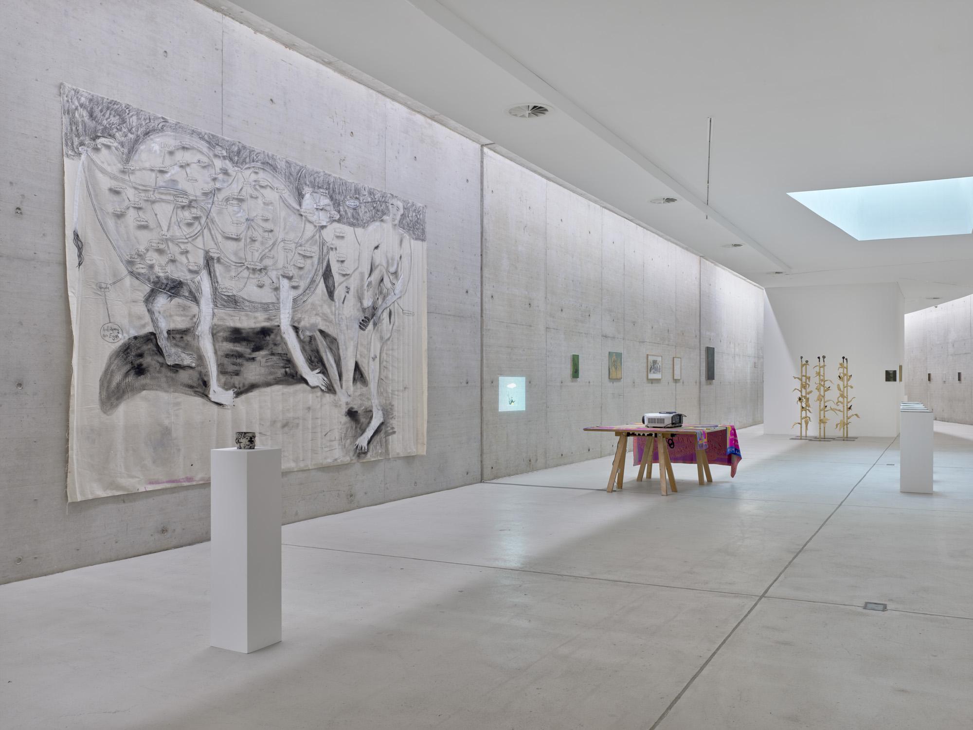 An der Wand hängt ein Gemälde aus Kohle und Acryl auf Leinwand. Verschiedene Sockel und ein Tisch stehen im Raum, im Hintergrund sind weitere Gemälde und Skulpturen zu erkennen.