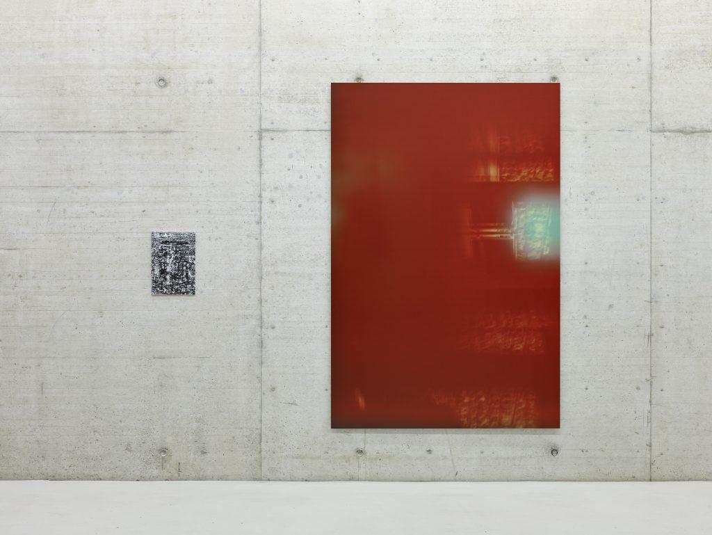 Eine kleine schwarz-weiße Fotografie und eine große rote Fotografie hängen an der Wand aus Sichtbeton.