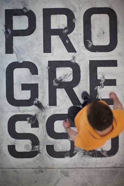 Eine Person ist von oben fotografiert, wie sie über den auf dem Boden angebrachten Schriftzug