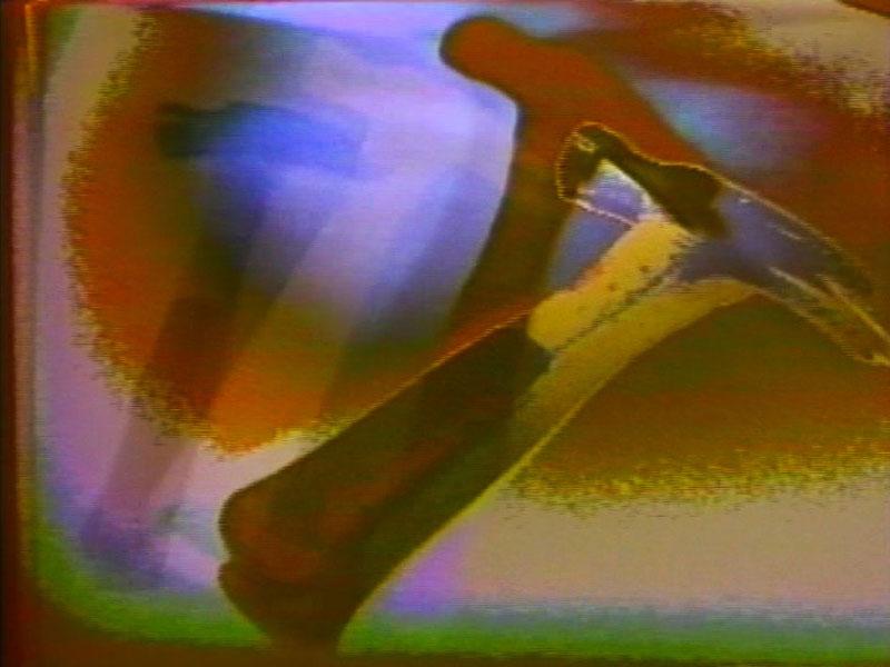 Videostill mit verschiedenen Farbflächen. Objekt ähnelt einem Hammer.