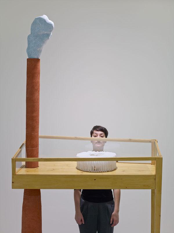 Person steht hinter einer Skulptur, die aus einem Schornstein mit Rauch und einem Körper, der einem Tisch ähnelt steht.