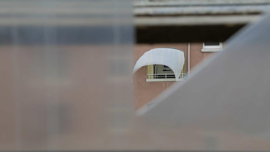 Hinter einer Folie ist ein Haus mit wehender Gardine.