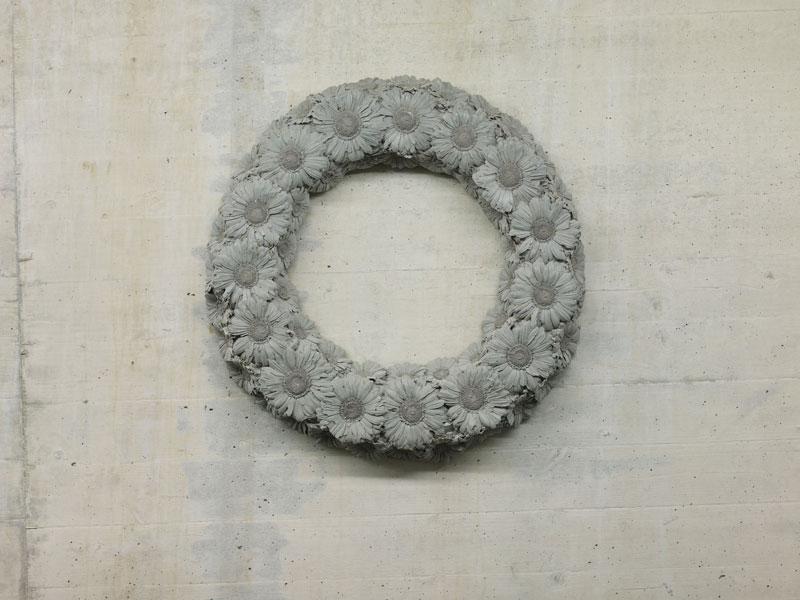 Kranz aus Beton, der aus Kamillenblütenabbildungen besteht.