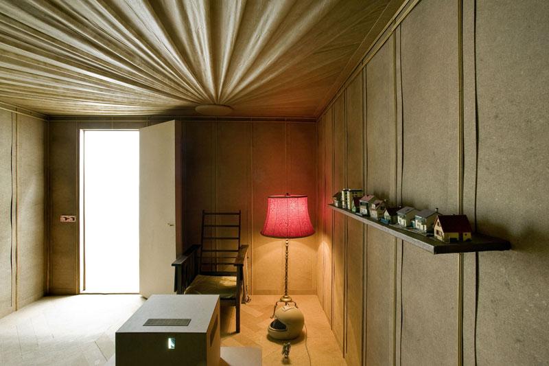 Raumeinsicht mit Stehlampe, Stuhl, einer Raumdecke aus Stoff und einem regal mit Miniaturhäusern.