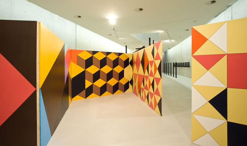 Wände, bemalt mit Würfeln, Dreiecken und geometrischen Mustern in Orange, braun, Rot, Gelb, Schwarz und Weiß sind in der Mitte des Raums platziert.