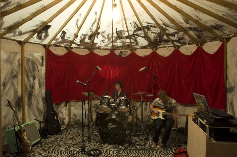 Zwei Personen spielen E-Gitarre und Schlagzeug in einem Zelt. Links befinden sich weiter Instrumente.