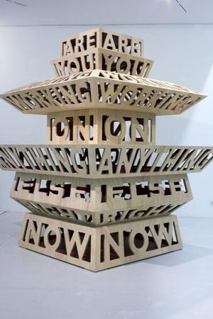 Skulptur aus Holz bestehend aus verschiedenen Etagen. In den Etagen sind die Wörter