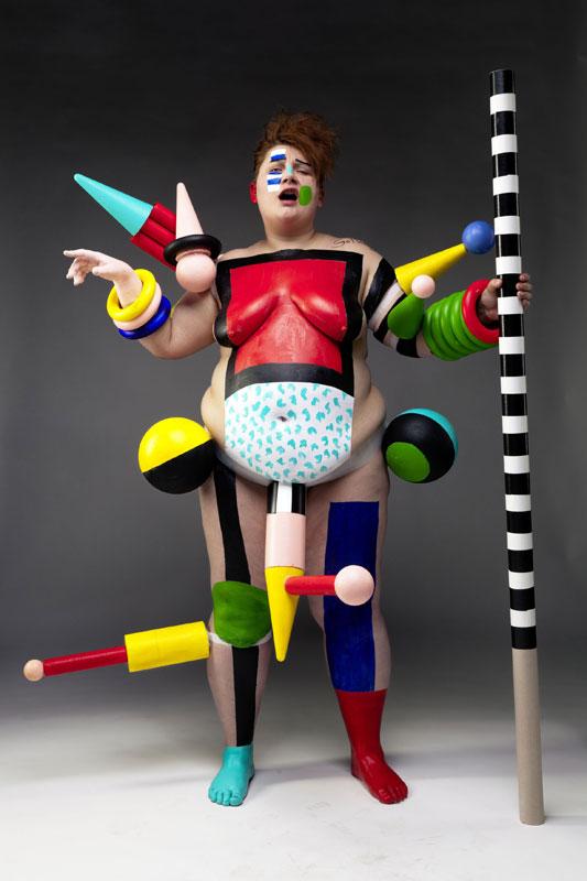 Eine Person ist mit verschiedenen geometrischen Formen bemalt und hat Objekte an ihrer Haut kleben. In ihrer linken Hand hält sie einen schwarz-weiß gestreiften Starb.
