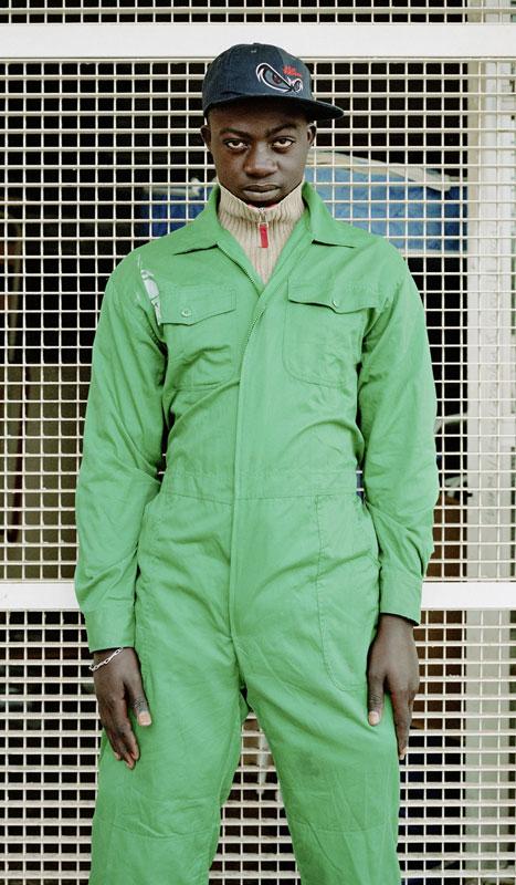 Mann mit Kappe und grünen Ganzkörperanzug steht vor einer Gittertür.
