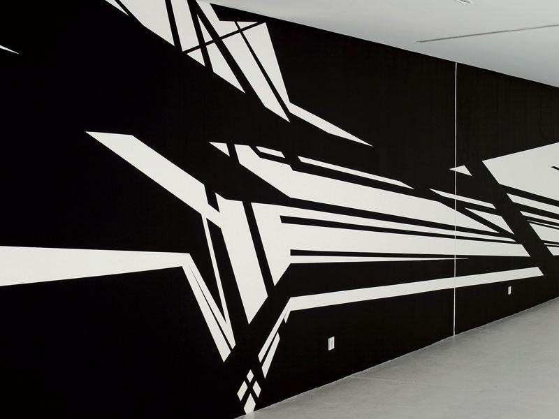 Schwarz-weiß Zeichnung auf der Wand des KITs, bestehend aus Linien und kantigen Formen.