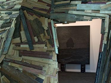 Holzstücke sind zu einer Wand arrangiert. Im Hintergrund ist ein dunkles Gemälde mit einem Baum zu erkennen.