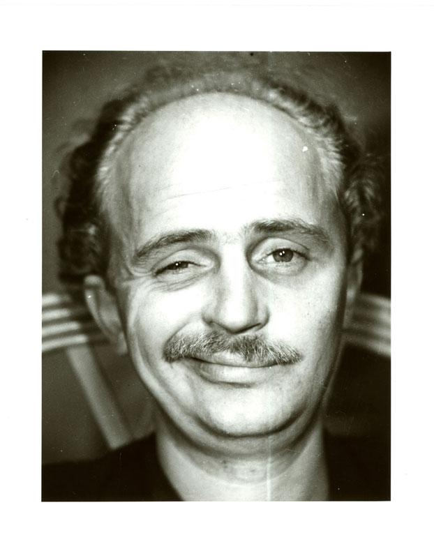 Fotografie eines Mannes, mit Schnauzbart, der zwinkert.