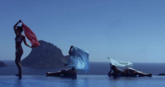 Drei Personen scheinen mit Tüchern zu tanzen und gefunden sich an der Kante eines Pools.
