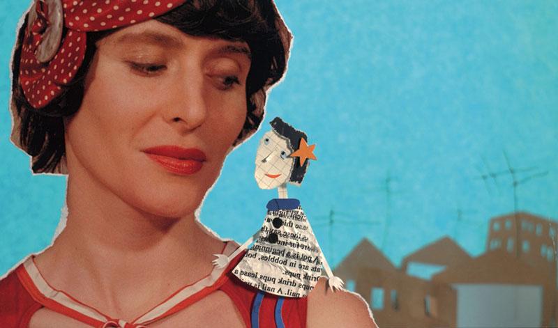 Frau mit einem roten Haarband hat eine Figur aus Zeitungspapier und anderem Papier auf ihrer Schulter sitzen.
